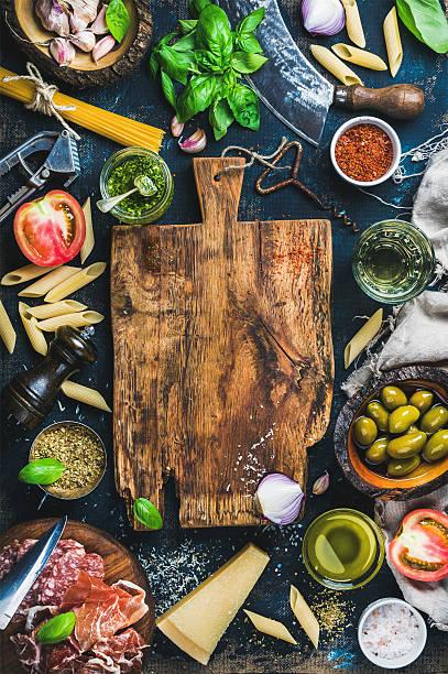 italian food cooking ingredients on dark background - italienische speisekarte stock-fotos und bilder