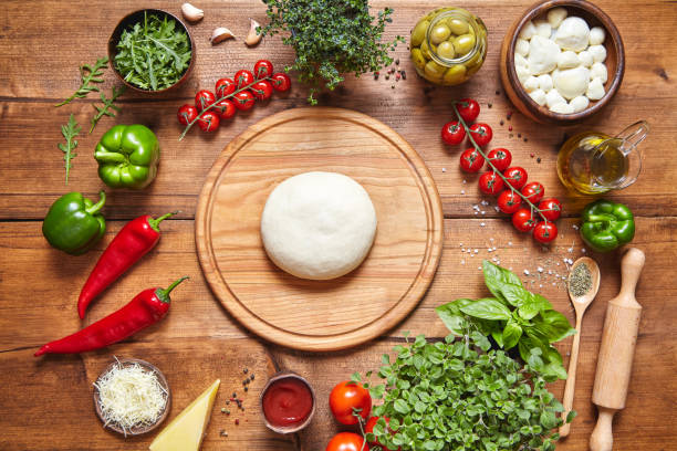 Italian food cuisine background. Pizza cooking ingredients: dough, mozzarella, tomatoes, basil, olive oil, cheese, sauce, regano, parmesan, pepper, herbs served on rustic wooden table. stock photo