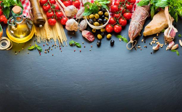 ingredientes de comida italiana na mesa escura com espaguete, tomate e queijo - comida italiana - fotografias e filmes do acervo