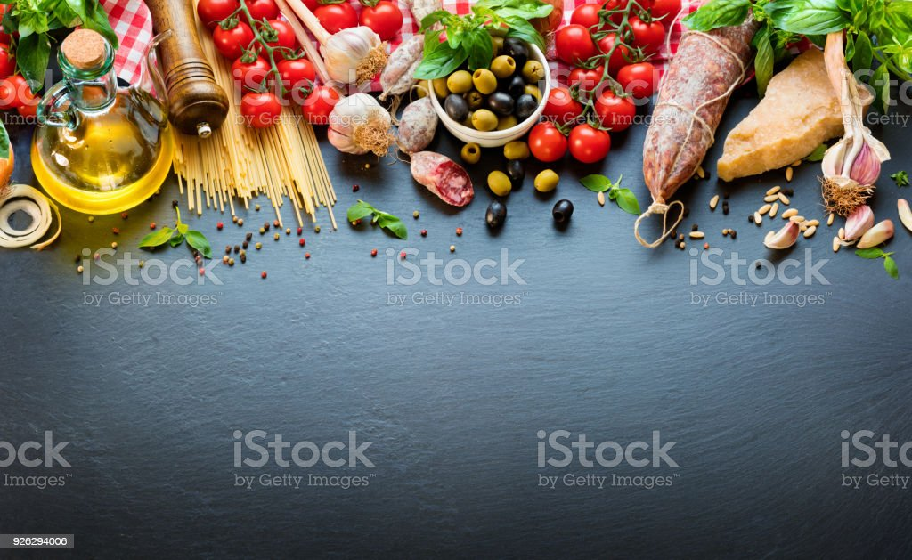 Italian Food Ingredients On Dark Table With Spaghetti, Tomato And Cheese stock photo