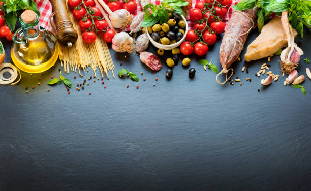 italian food ingredients on dark table with spaghetti, tomato and cheese - italian food stock photos and pictures