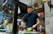Shot of a young man preparing a steak tartare dish in a commercial kitchen