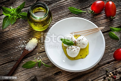 Italian food: high angle view of a small white plate with three fresh bocconcini shot on rustic wooden table. Olive oil, fresh ripe tomatoes and basil leaves complete the composition. Bocconcini are small buffalo's milk mozzarella balls usually served as appetizer in Italian cuisine. Predominant color are white, green and brown. Low key DSRL studio photo taken with Canon EOS 5D Mk II and Canon EF 100mm f/2.8L Macro IS USM