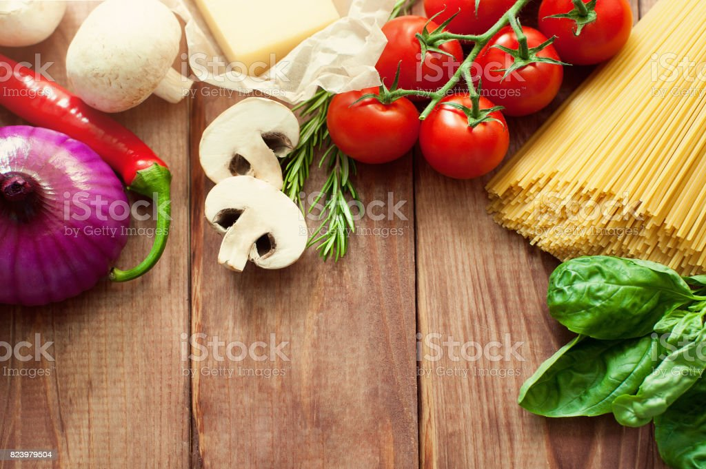 Italian food or ingredients background with fresh vegetables, pasta, cheese parmesan and spices. Top view, view from above. Copy space. Dark background. stock photo