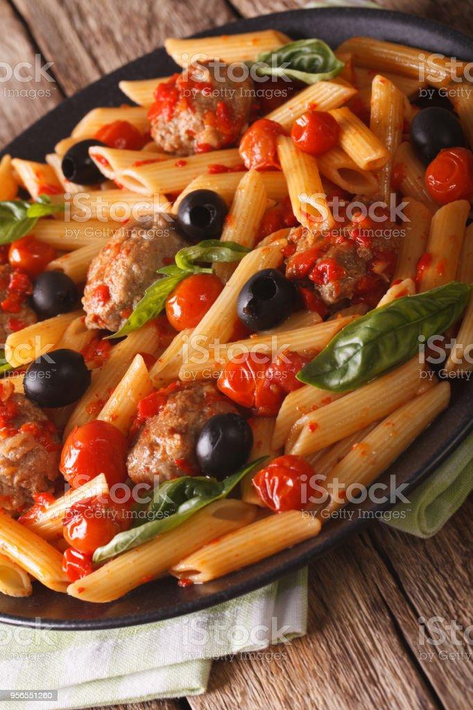 Italienische Küche: Pasta mit Fleischbällchen, Oliven und Tomaten Sauce Closeup. Vertikal - Lizenzfrei Abnehmen Stock-Foto