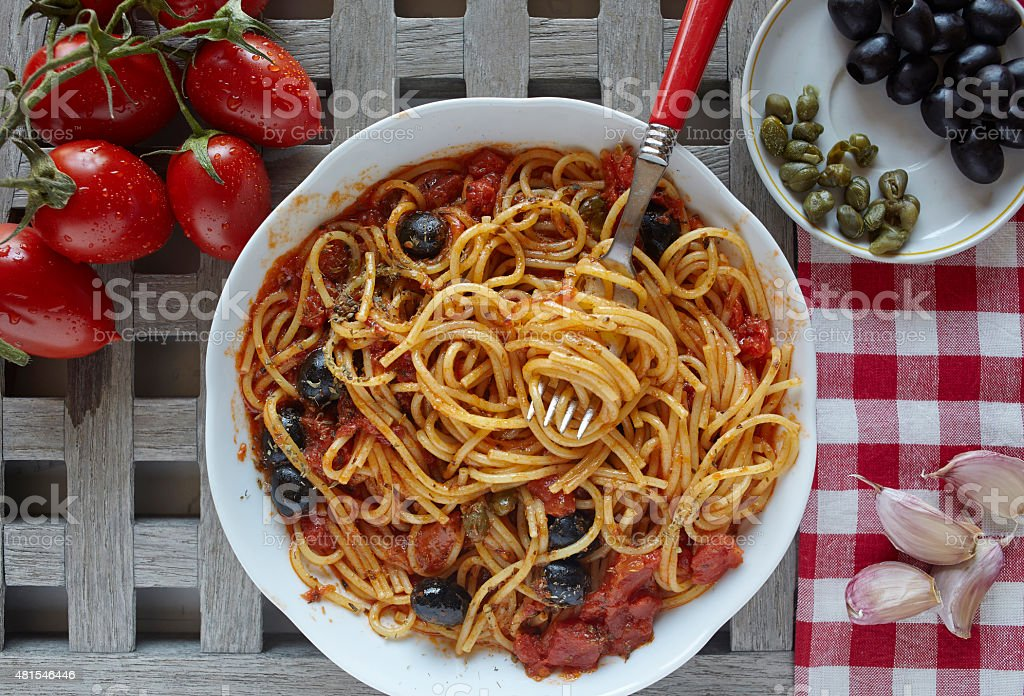 italian food: pasta with tomatoes, olives and capers, called put stock photo
