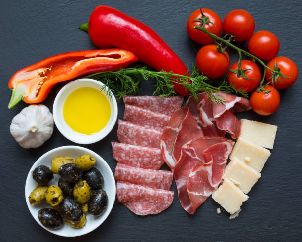 Italian Food Table top shot of Mediterranean Italian foods with cold cuts meats such as salami and copocollo, along with parmesan cheese and vegetables (garlic, olives, red peppers and tomatoes). ketogenic diet stock pictures, royalty-free photos & images