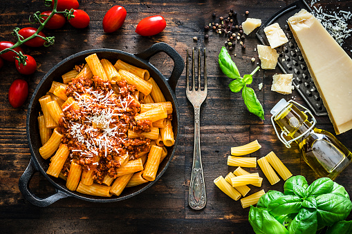 Italian food: rigatoni pasta with bologna sauce served in a cast iron pan shot from above on rustic wooden table. Parmesan cheese placed on a grater, fresh tomatoes, basil and an olive oil bottle complete the composition. High resolution 42Mp studio digital capture taken with Sony A7rII and Sony FE 90mm f2.8 macro G OSS lens
