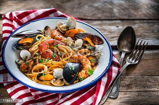 Typical Italian food: seafood pasta plate shot from above on rustic wooden table.  The plate is at the left placed on a red and white checkered tablecloth. XXXL 42Mp studio photo taken with Sony A7rii and Sony FE 90mm f2.8 macro G OSS lens