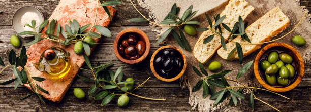 Italian food with Olives, Sliced bread Ciabatta and Olive Oil on gray wooden background stock photo