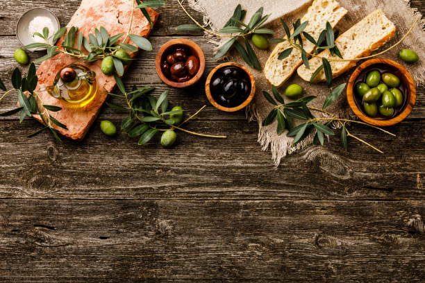 italian food with olives, sliced bread ciabatta and olive oil on gray wooden background copy space - ramoscello d'ulivo foto e immagini stock