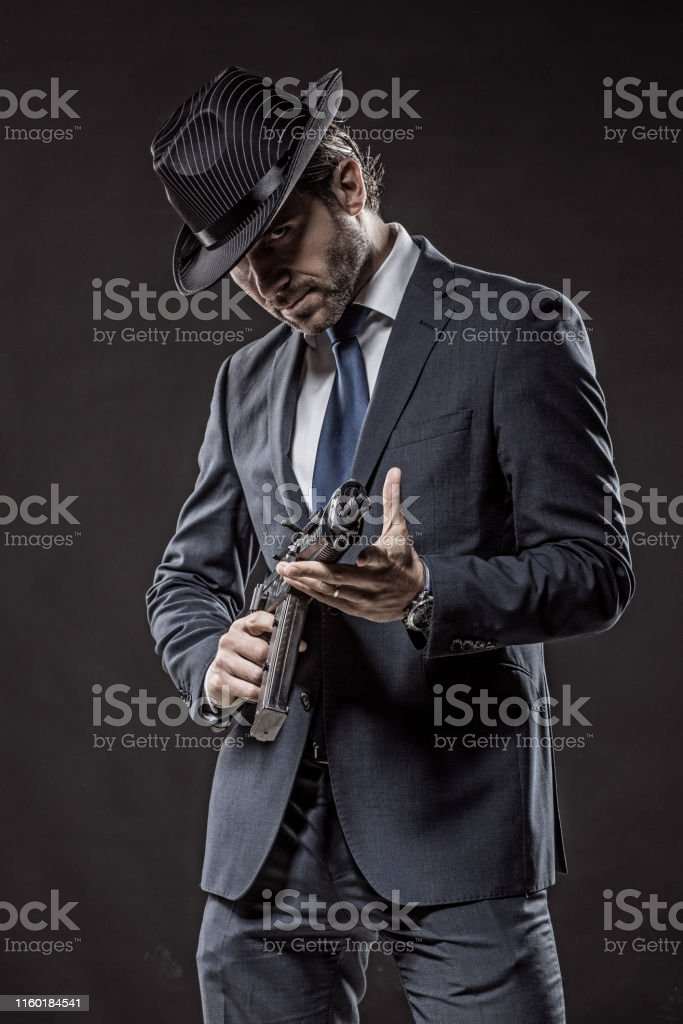 Italian Gangster Mafia Man holding guns in smoky studio shoot