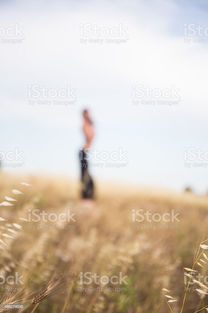 Italian girl stands in countryside. Out of focus stock photo