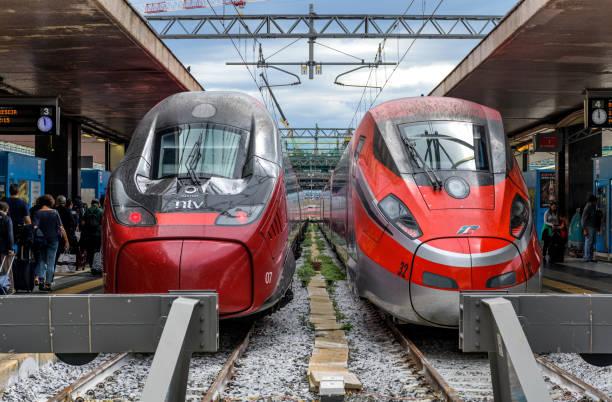 Italienische Hochgeschwindigkeitszug - zwei rote moderne elektrische Hochgeschwindigkeitszüge, Alstom Pendolino der NTV auf der linken Seite und Frecciarossa 1000 von Trenitalia auf der rechten Seite, am Bahnsteig des Bahnhofs Rom Termini nebeneinander pa – Foto