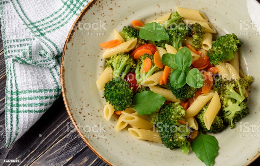Italian home cooking. Vegetable pasta with broccoli, cherry tomatoes, carrots, garlic and basil. Top view stock photo