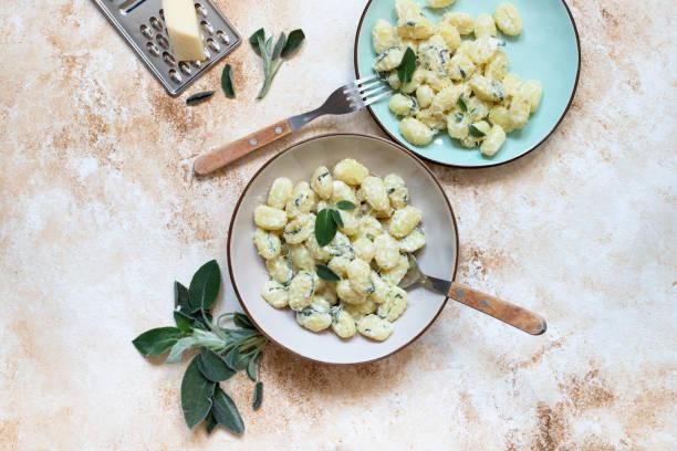 italienische hausgemachte gnocchi mit butter, käse und salbei serviert in zwei tellern auf einem hellen marmortisch. italienischeküche. kopieren sie den speicherplatz. flache verlegung - ricotta stock-fotos und bilder