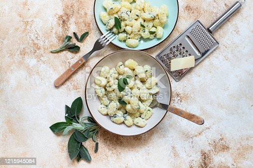 Italian homemade gnocchi with butter, cheese and sage served in two plates on a light marble table. Italian food. Copy space. Flat lay