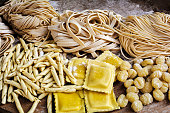 Retro styled photograph of flour blushed spaghetti, tagliatelle, fettuccine, linguine, ravioli on an old wooden table