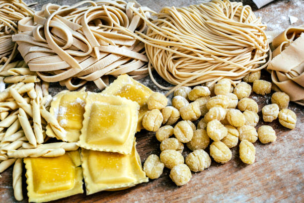 Italian homemade pasta Retro styled photograph of flour blushed spaghetti, tagliatelle, fettuccine, linguine, ravioli on an old wooden table spaghetti straps stock pictures, royalty-free photos & images