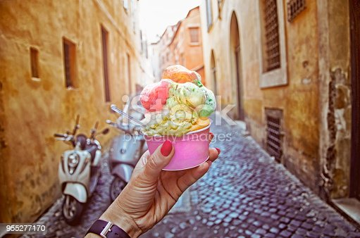 Italian ice - cream cone held in hand on the background of on vintage street atmosphere in Rome , Italy