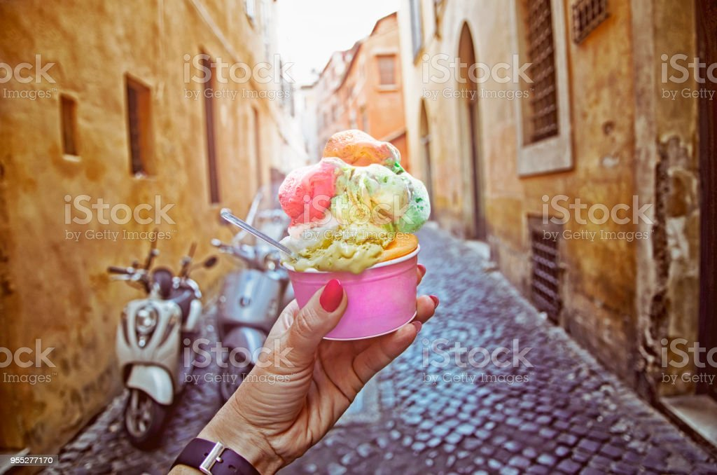 Italian ice - cream cone held in hand on the background of on vintage street atmosphere stock photo