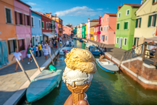 Hands holding  two flavours ice cream in waffle cone in Burano, Italy