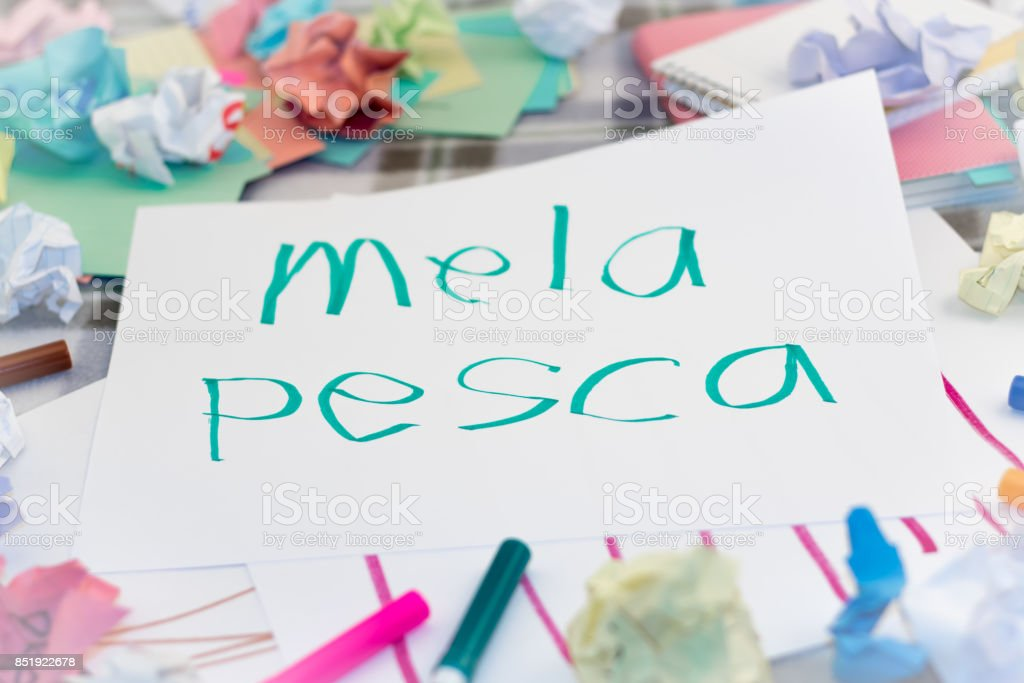 Italian; Kids Writing Name of the Fruits for Practice (Translation; Apple, Peach) stock photo
