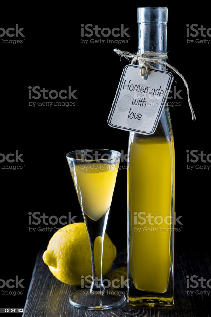 Italian limoncello in a shot glass on a black wooden background stock photo