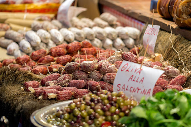 Italian market stall with wild boar salami and olives Italian market stall with wild boar salami and olives umbria stock pictures, royalty-free photos & images
