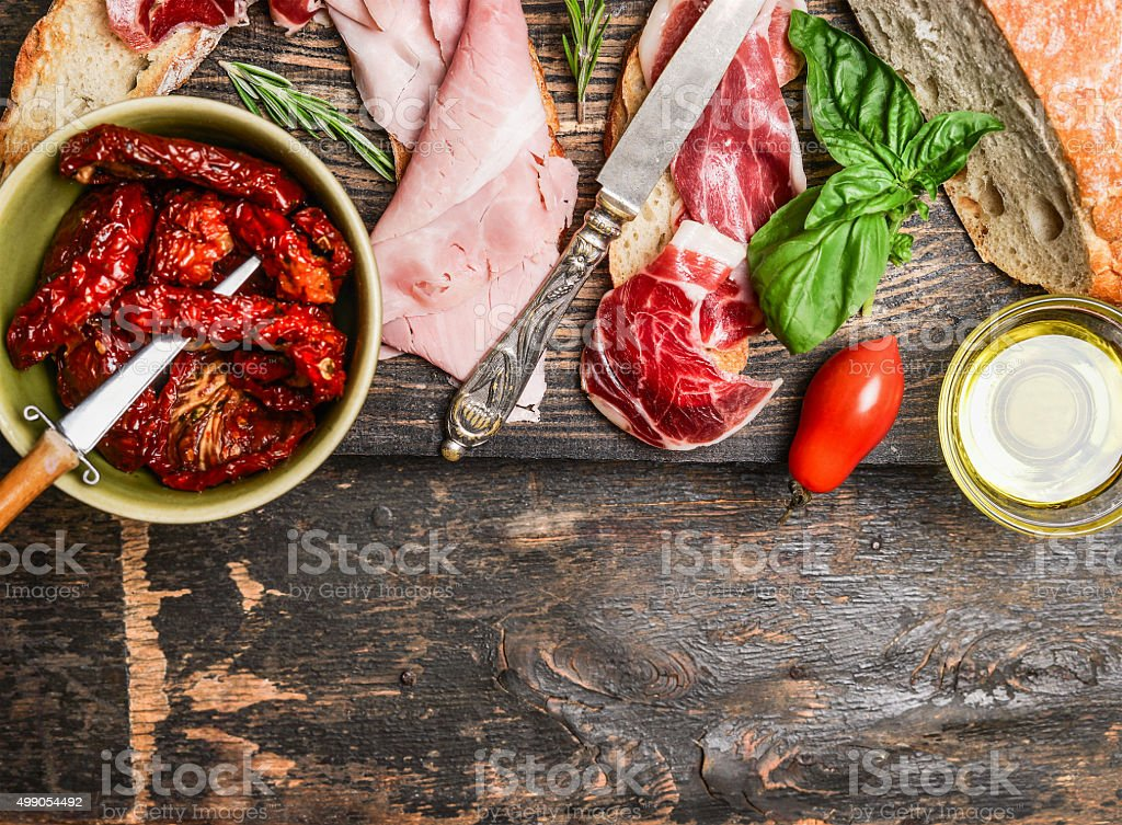Italian meat plate with bread and antipasti on wooden background stock photo