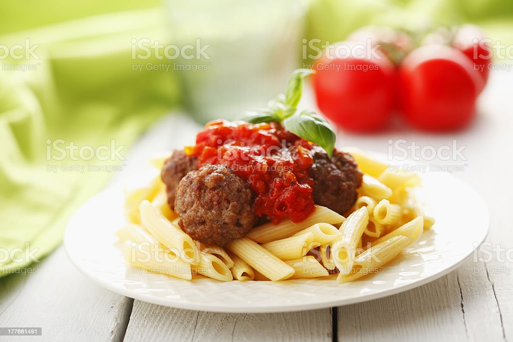 Italian meatballs with penne pasta in tomato sauce stock photo