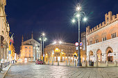 Piacenza, Italy - April 20, 2017: Emilia Romagna, northern Italy, important city of the Po Valley.  Main square of Piacenza in the evening. Piazza Cavalli (Square horses), to the right palazzo Gotico (Gothic palace), in the center church of San Francesco ( 14th century). On the left you can see via XX Settembre which leads to Piazza Duomo with the Cathedral of Piacenza (Duomo di Piacenza)