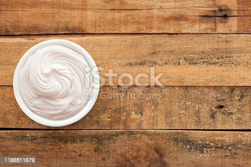 Top view of white bowl full of italian meringue over wooden table