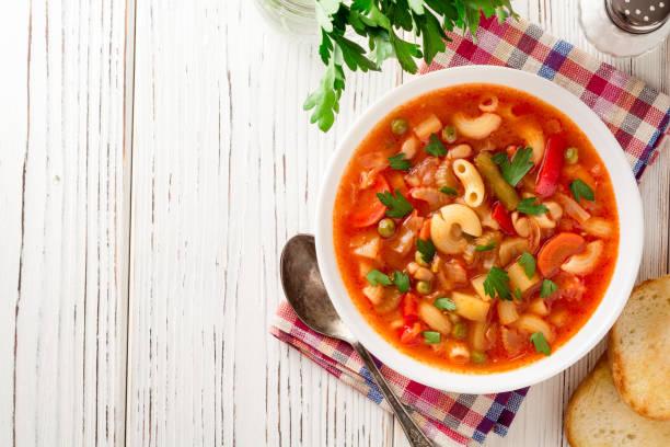 italian minestrone soup on white wooden background. - minestrone foto e immagini stock
