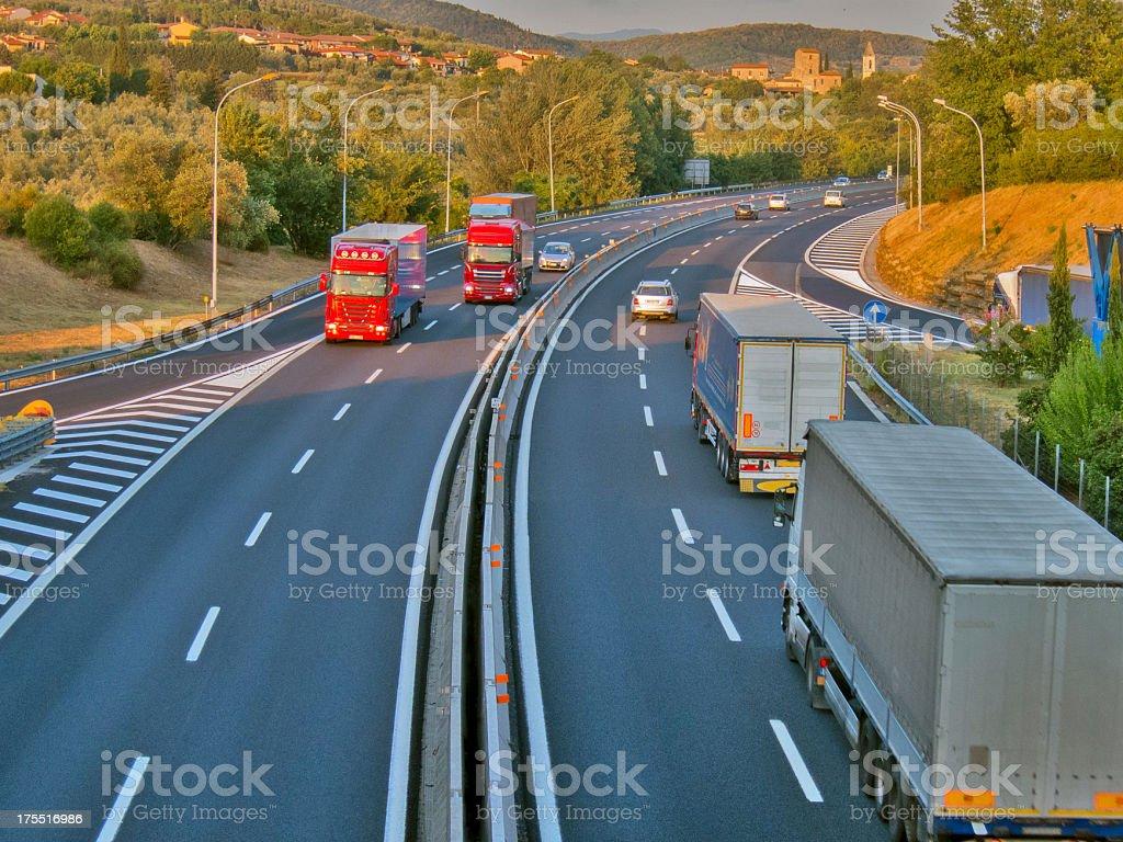 Italian motorway, trucks travelling, green hills around royalty-free stock photo