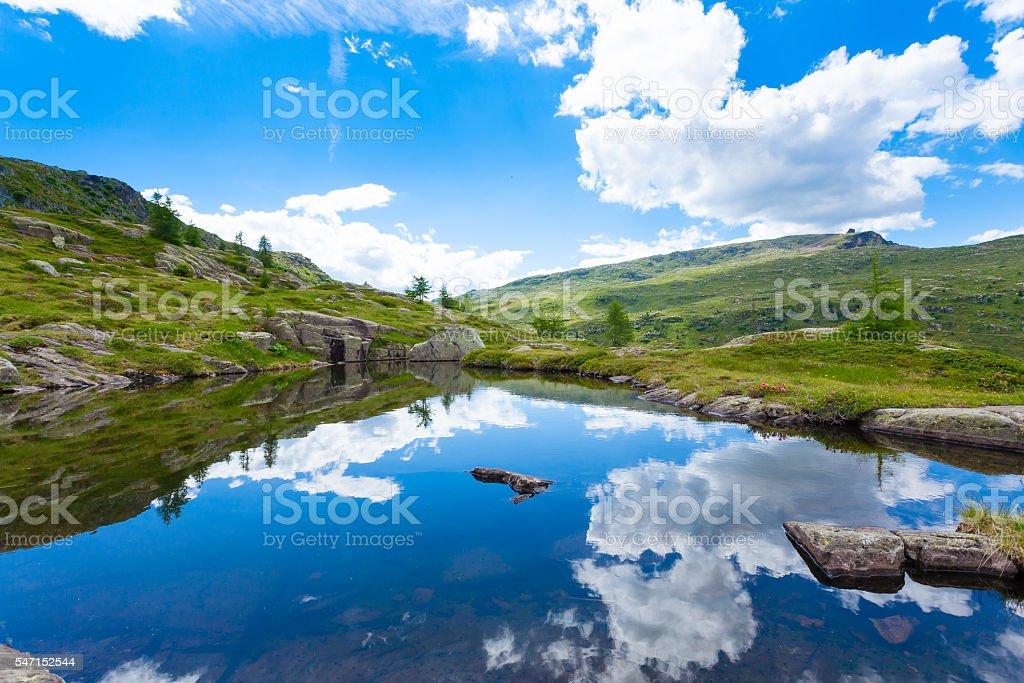 Italian mountain panorama, clouds reflected on alpine lake stock photo
