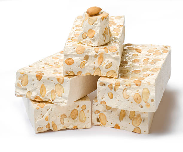 Italian nougat with almonds, pieces on white background stock photo