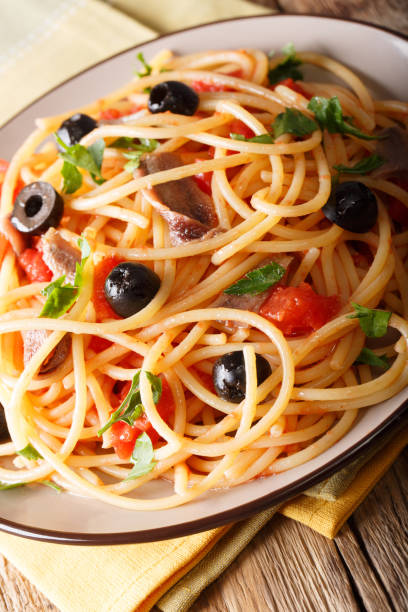 Italian pasta Alla Puttanesca with anchovies, tomatoes, garlic and black olives macro. vertical stock photo