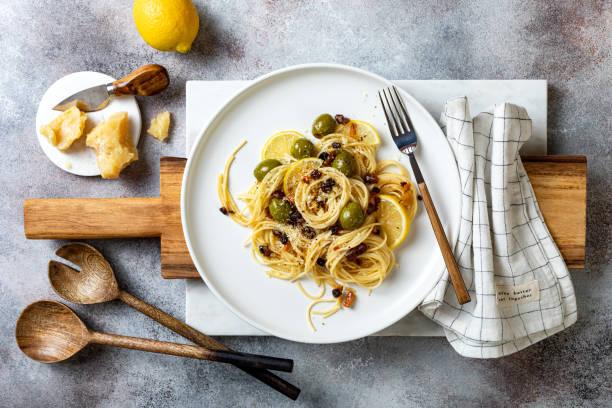 Italienische Pasta cacio e pepe, Spaghetti gemischt mit geriebenem Käse, grüne Oliven, Zitrone und Rosinen – Foto