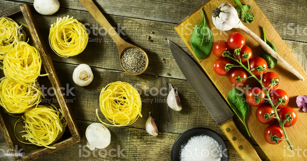 Pastas italianas, tomates cherry, ajo, setas y especias en una rústica mesa de madera. foto de stock libre de derechos