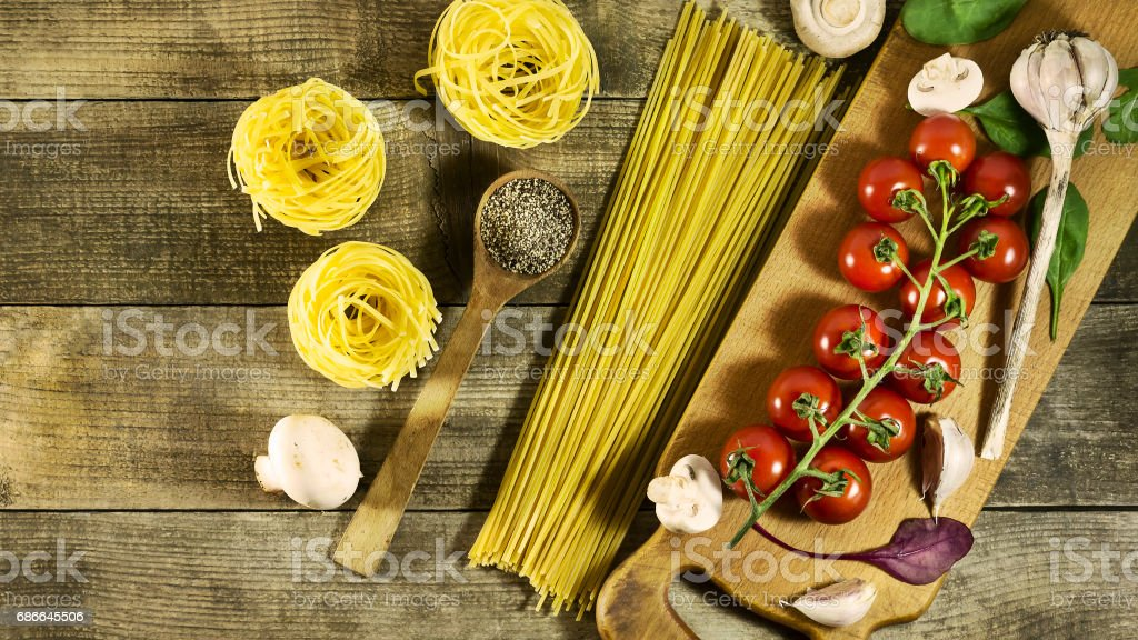 Italian pasta, cherry tomatoes, garlic, mushrooms and spices on a rustic wooden table. royalty-free stock photo