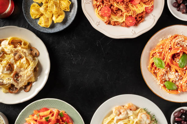 Italian pasta dishes forming a frame for copy space, overhead shot on a dark background. Pastas with meat, vegetables, seafood, chicken and mushrooms stock photo