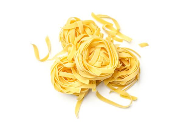nido di fettuccine di pasta italiana isolato su sfondo bianco. vista dall'alto - pasta foto e immagini stock