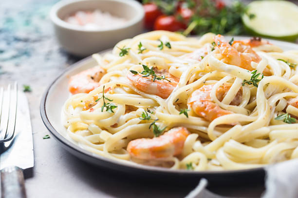Italian pasta fettuccine Italian pasta fettuccine in a creamy sauce with shrimp on a plate, close-up. pasta photos stock pictures, royalty-free photos & images