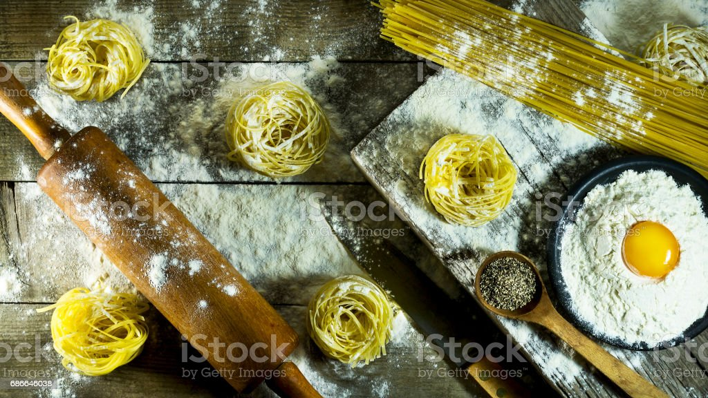 Italian pasta, flour and raw egg on a rustic wooden table. royalty-free stock photo