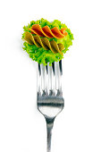 Italian pasta fusilli with lettuce leaves on a fork just for eating over a white background.