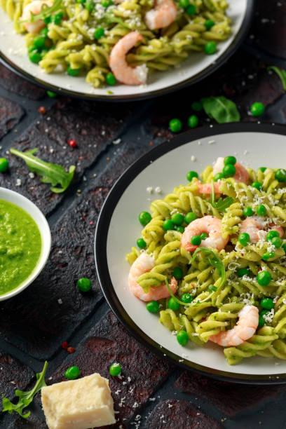 massa italiana em um molho cremoso do pesto com camarão, camarões - fine dining - fotografias e filmes do acervo