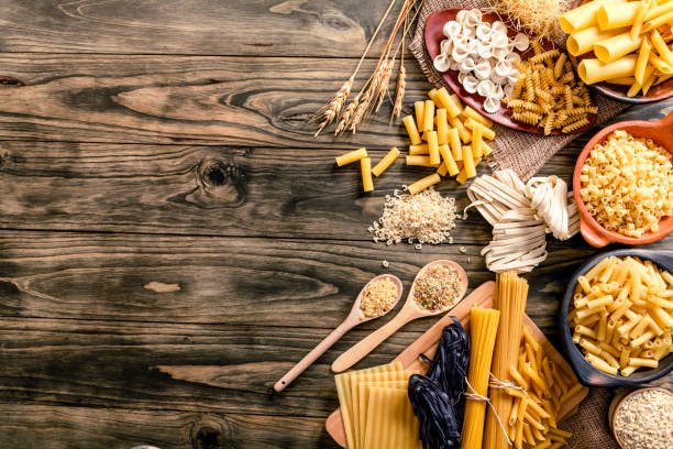 Italian pasta on rustic wooden table in a kitchen Assorted pasta including Spagetti, Linguini, Fetuccini, Farfalle, Anelli, Penne, Fusilli, Macaroni, Conchiglie, Rigatoni, Orzo,  Stortini, Letters, Vermicelli, Fetuccini, black Fetuccini and Pasticcio. Space for text on table. uncooked pasta stock pictures, royalty-free photos & images