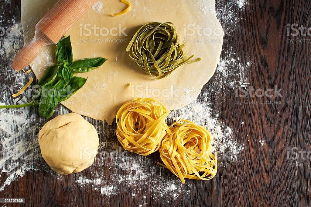 Italian pasta on wooden table with dough stock photo