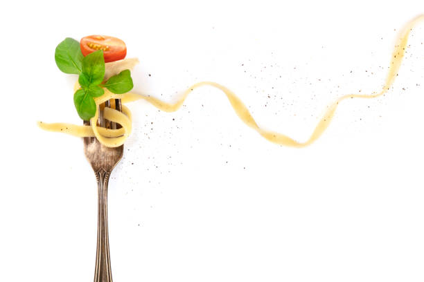 Italian pasta. Overhead photo of vintage fork with pappardelle, basil, cheese, and tomato, on white background Italian pasta. An overhead photo of a vintage fork with pappardelle, basil, cheese, tomato, and pepper, on a white background with copyspace fine dining stock pictures, royalty-free photos & images
